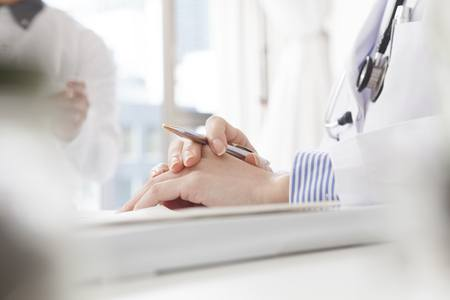 Hands of medical professional and clipboard