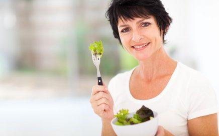 attractive mature woman with fresh green salad at home